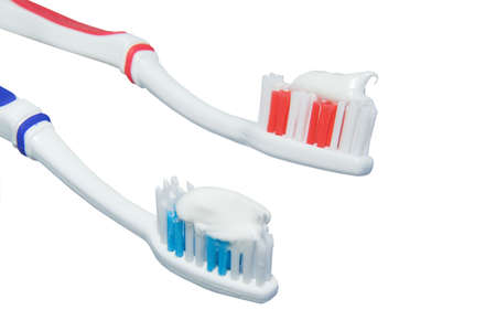 His and hers toothbrushes loaded with toothpaste