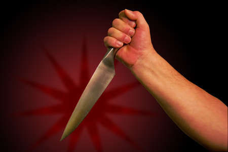 A hand holds a knife ready to stab. With clipping path so you can easily remove from background,