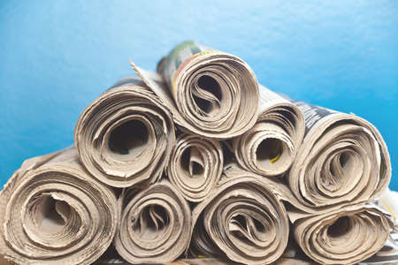 rolled up: A stack of old rolled up newspapers with a blue background