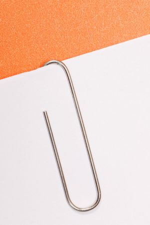 paper clip fastened to white paper with orange background photo