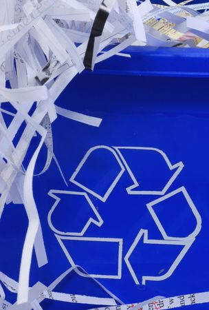 segregate: shredded paper spilling out of blue recycle bin Stock Photo