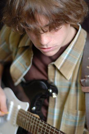 rebeldia: catorce años de edad, muchacho jugando su guitarra eléctrica