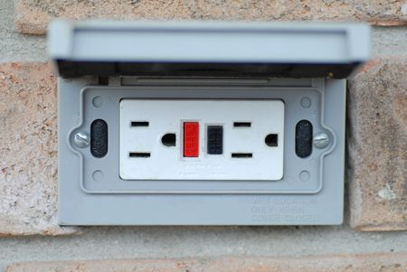 receptacle: grounded outdoor electrical socket on brick wall