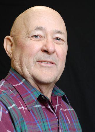 portrait of bald senior man on black background