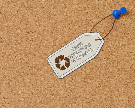 recycled material tag attached to corkboard with thumb tack photo