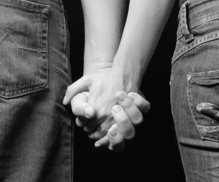 clasps: engaged couple holding on hands - view from backside Stock Photo