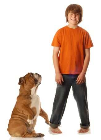 stocky: young teen boy standing beside dog that is begging at his side