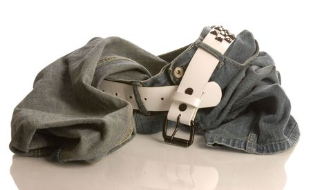 heap: pair of blue jean with a belt taken off and left in a heap Stock Photo
