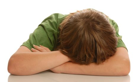 punish: young teenage boy with head down in arms