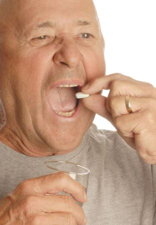 senior man taking medication with glass of water photo
