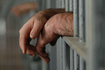 criminals: mans hands behind bars in jail or prison Stock Photo