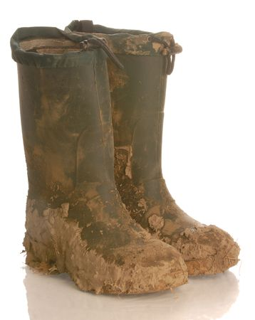 hiking boots: muddy rubber boots isolated on a white background