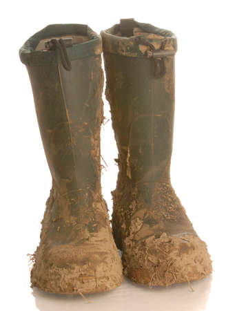 gritty: muddy rubber boots isolated on white background