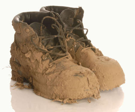 gritty: muddy work boot isolated on a white background Stock Photo
