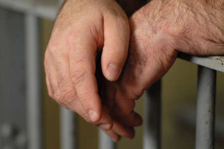 prisoner man: mans hand behind bars in jail or prison Stock Photo