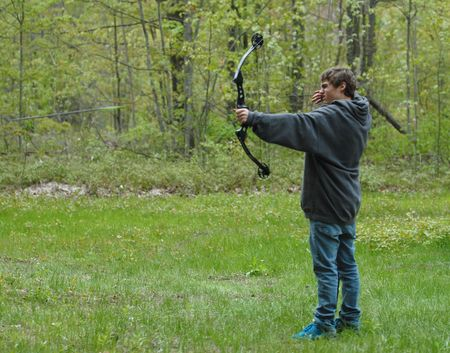 compound: teenage boy shooting compound bow with arrow in the scene Stock Photo