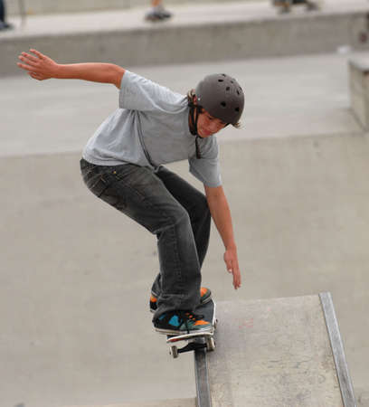 youth culture: teenage skateboarder doing 50 50 grind on a rail