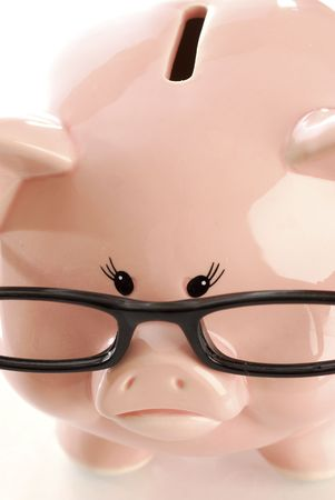 pink piggy bank with sad expression wearing black rimmed glasses on white background photo