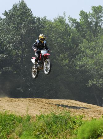 teenage boy jumping hills on a dirt bike  photo