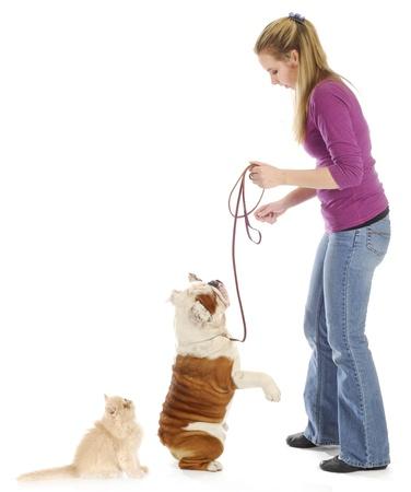 obediencia: mujer con perro sobre Correa y gatito buscar a ella con una reflexión sobre fondo blanco Foto de archivo