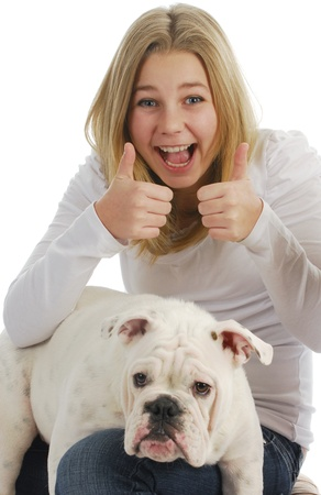 teenage girl giving thumbs up with her dog on her lap on white background photo