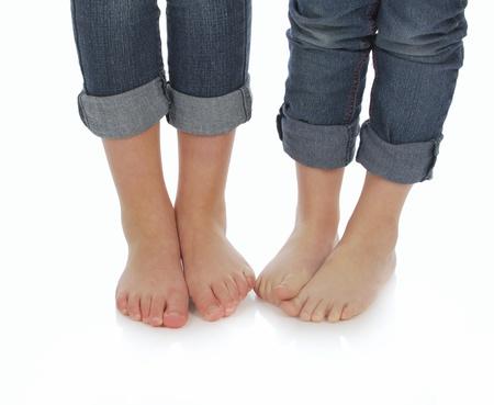 scalzo ragazze: piedi nudi - due sorelle standind accanto a altro con i piedi nudi su sfondo bianco