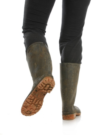 muddy boots - woman walking away with muddy boots on white background photo