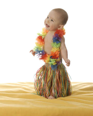 six month old baby dressed up wearing hawaiian skirt and lei Stock Photo
