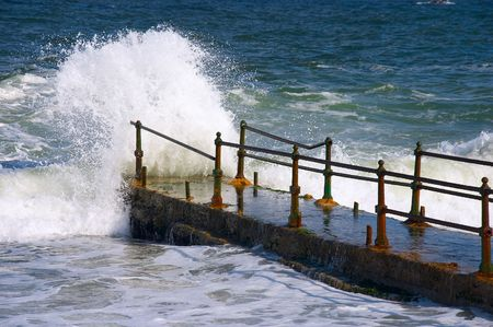 Waves of the sea hitting about quay in storm weather photo