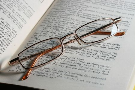 Glasses laying on page of the open book Stock Photo