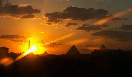 Pyramids and a mosque on a background of a sunset with the cloudy sky Stock Photo