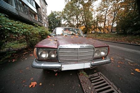 abandoned city: Old damaged sedan on the city street Stock Photo