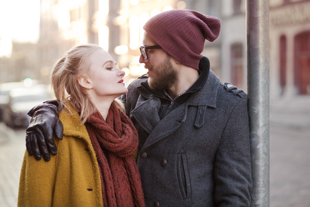 Young smiling happy hipster couple hugging in winter photo