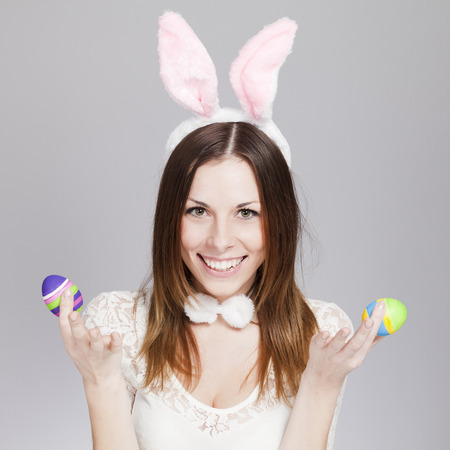 fluffy ears: Brunette smiling and holding painted easter eggs