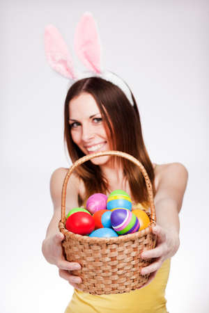 Brunette smiling and holding easter egg basket photo