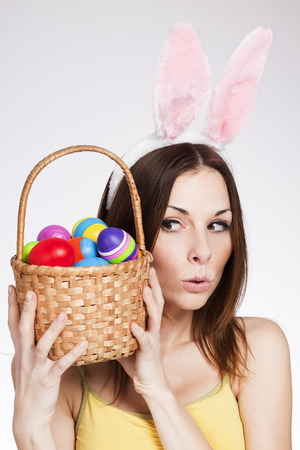 Beautiful young Brunette holding easter egg basket photo