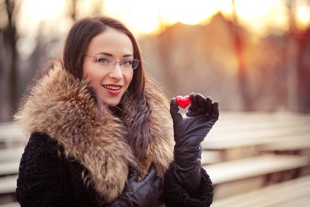 Pretty woman holding red heart on Valentines day photo