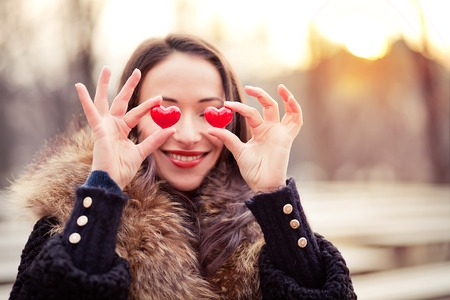 Pretty woman holding red hearts on Valentines day photo