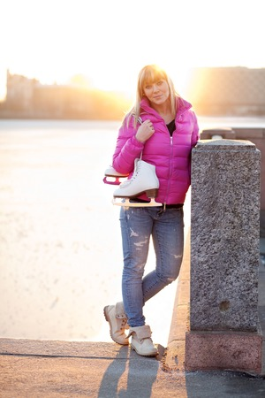 exhalation: Beautiful young blond woman standing with her ice skates