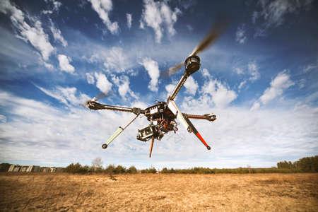 航空機: 飛行ドローンは青い空でビデオを撮影しています。 写真素材