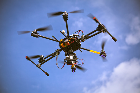 drone: Flying helicopter drone is filming video in the blue sky