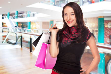 Pretty girl with bags is enjoing discounts in the shopping center mall photo