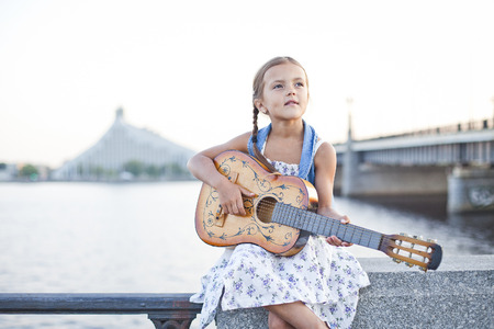 young musician: Girl playing guitar on river embankment