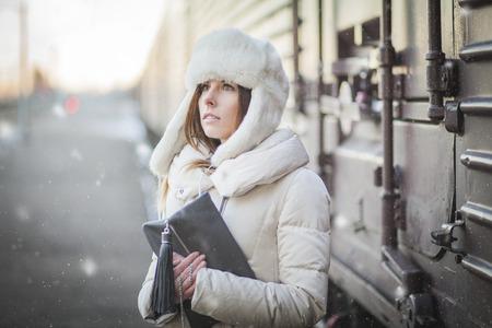 railroad station: Pretty girl in winter blizzard on railroad station