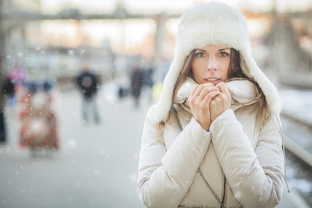 Youn woman on a train station in winter photo