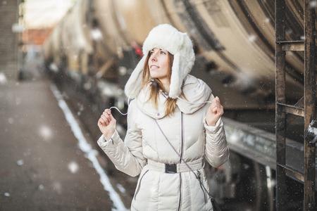 a blizzard: Pretty girl in winter blizzard on railroad station