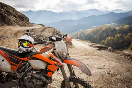 dirt bikes: Dirty enduro motorcycle motocross helmet on road Stock Photo
