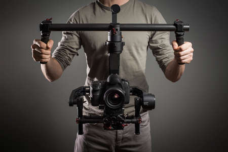 slr camera: Professional videographer with gimball video slr Stock Photo