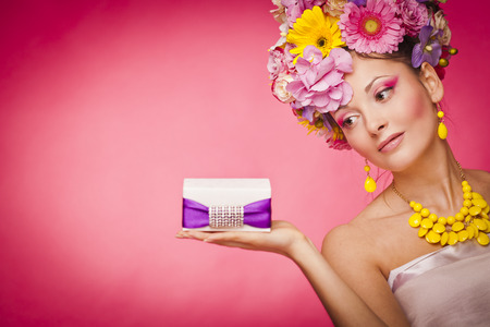 abstract eye: Young healthy woman holding gift box on her palm
