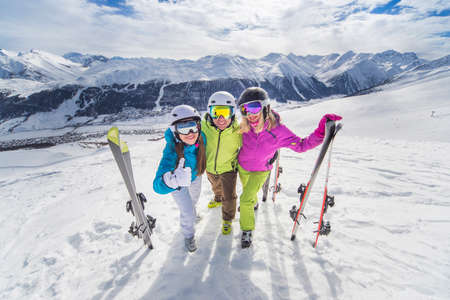 Female and male young people having skiing and snowboarding vacation on a snow slopes